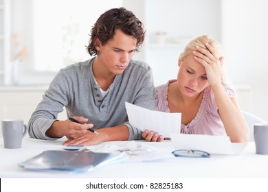 Worn out couple listing expenses in the living room