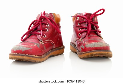 Worn out kiddie-size red lace-ups. Isolated on white background with shadow reflection. Children's shoes with laces. Small babie's booties on reflective underlay. Old ankle boots for small kid.