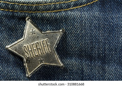 Worn Out Old Sheriff Badge on Blue Denim Horizontal Photograph
