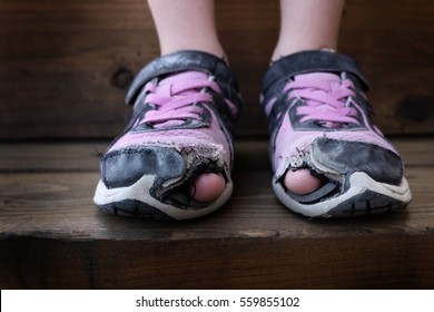 Worn out old shoes with holes in the toes used by homeless child