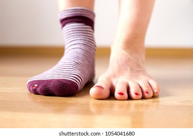 Worn out socks with a toe sticking out over a wooden background