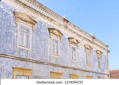 Worn paint creating an interesting distressed texture on the facade of this portuguese building with a roof top balustrade and pediment window architecural features