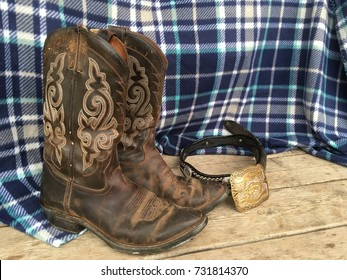 Worn pair of cowboy boots and belt with a rustic back droop