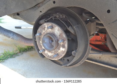 Worn rear drum brakes coated with brake dust from use.