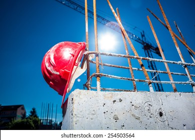 Worn Red Hard Hat reinforced concrete steel with big crane and sun in background on a construction site
