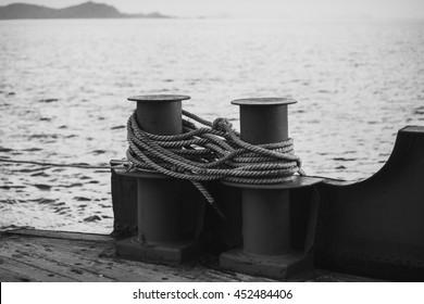 Worn rusty mooring bollards with rope on sea background.