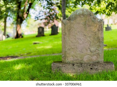 A worn sandstone grave marker in the shade on a very bright day. There is no text visible on the stone, but there is some moss on the top.