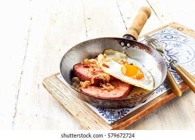 Worn skillet with serving of german breakfast with fried egg and two slices of country style ham