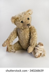 An worn vintage teddy bear with a bandaged foot