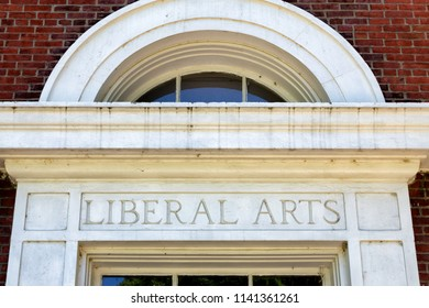 Worn and weathered liberal arts lettering on brick wall.
