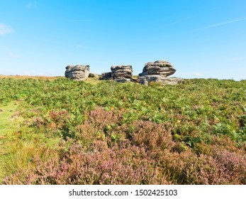 The worn and weathered Three Ships gritstone outcrop on Birchen Edge in the Derbyshire Peak District.