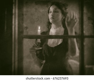 Worn wet plate photo of victorian woman holding candlestick looking out rainy window.