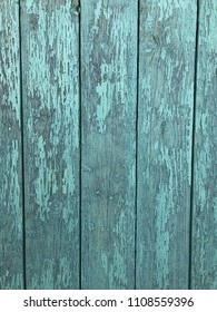 Worn wooden barn wall planks in green color with shown paint flakes. As background.