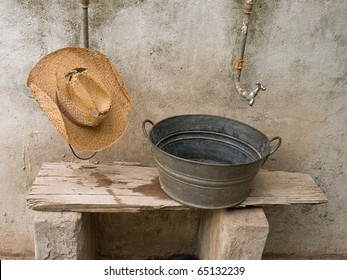 A worn-out straw hat hanging on a pipe and an antique basin standing on an aged wooden plank, below a faucet. A mildew wall is on the background.