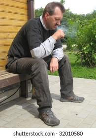 Worried adult man, sitting outdoor and smoking