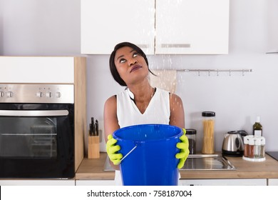 Worried African Woman Holding Bucket While Water Droplets Leak From Ceiling In Kitchen