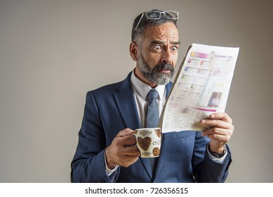 Worried and anxious senior business man looking at the newspaper with shock and terror on his face