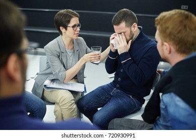 Worried or ashamed man crying and hiding his face while counselor offering glass of water to him