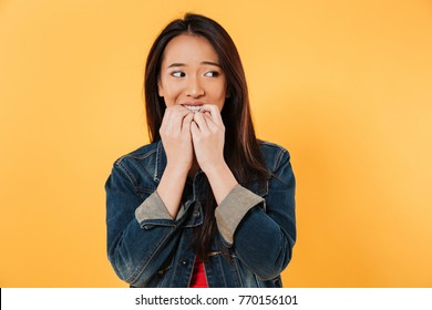 Worried asian woman in denim jacket bites her fingers and looking away over yellow background