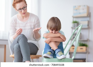 Worried autistic boy sitting with crossed legs on mint chair during conversation with psychiatrist