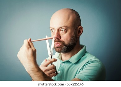 Worried bearded middle-aged  man with long nose isolated on blue wall background. Liar concept. He wants to cut nose