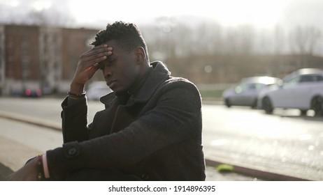 Worried black man suffering alone in emotional pain outside in city sidewalk street