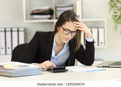 Worried bookkeeper calculating expenses with a claculator at office