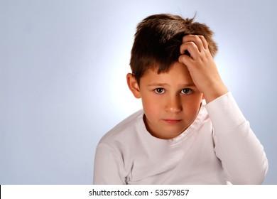 worried boy scratching his head