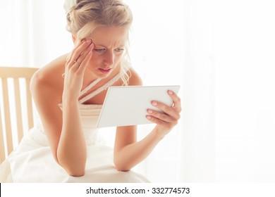 Worried bride looking at tablet