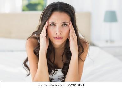 Worried brunette sitting on bed at home in bedroom