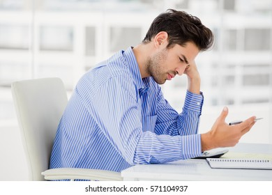 Worried businessman calculating accounts on a calculator in office