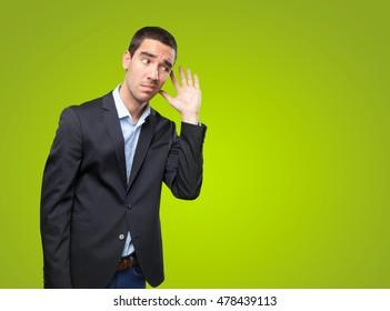 Worried businessman with hear gesture on green background