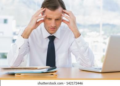 Worried businessman holding his head in his office