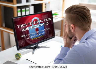 Worried Businessman Looking At Computer With Ransomware Word On The Screen At The Workplace