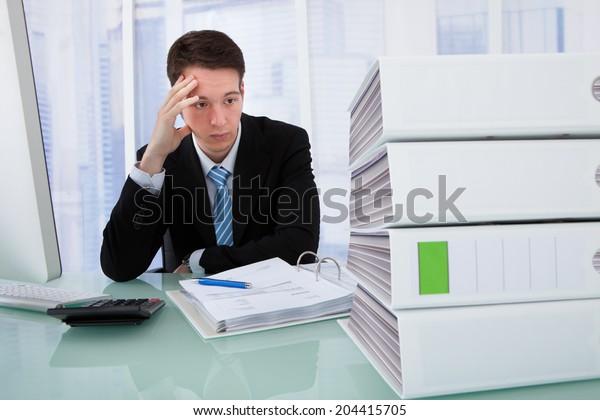 Worried businessman looking at stacked binders on office desk