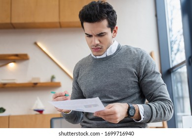 Worried businessman with pencil looking at paper in office