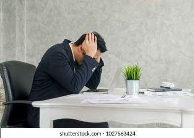 Worried businessman in suit sitting at office with burnout syndrome at desk.