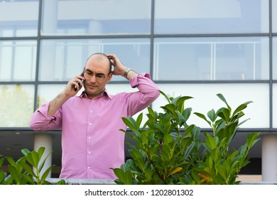 Worried businessman talk on mobile in front of building