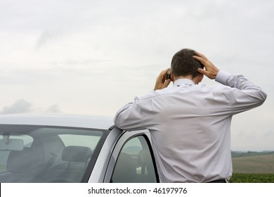 Worried businessman talking on cell phone beside his car