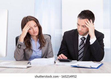 Worried Businessman And Woman Calculating Bills At Desk In Office