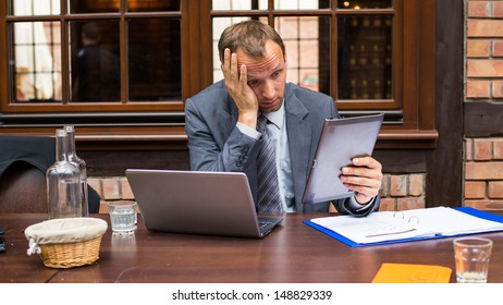 Worried businessman working in restaurant.