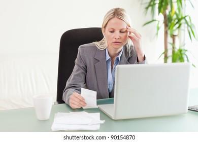 Worried businesswoman checking a bill