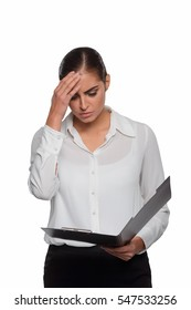 Worried businesswoman with a headache during her hard working day. Female holds her hand on the head and looks at the plan in a folder.