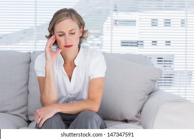 Worried businesswoman sitting on couch