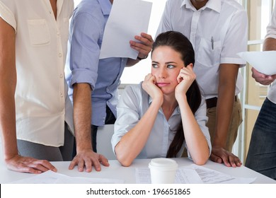 Worried businesswoman surrounded by colleagues in the office