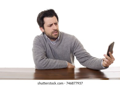worried casual man with a phone, on a desk, isolated
