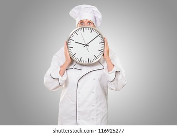 worried chef hiding behind a clock against a grey background