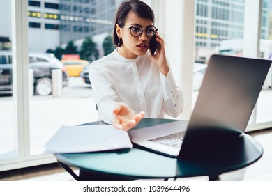 Worried concentrated female shocked with software failure during work at laptop calling to customer support explaining problem.Angry businesswoman disappointed with financial news talking on mobile
