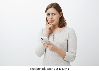 Worried and concerned girl feeling anxious parent find out daring photos leaked in social networks looking nervously and troubled at camera frowning biting finger while panicking holding smartphone