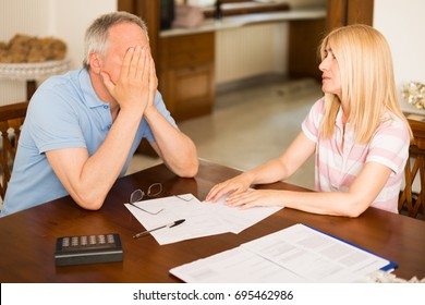 Worried couple calculating their expenses together